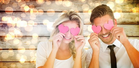 Composite image of attractive young couple holding pink hearts