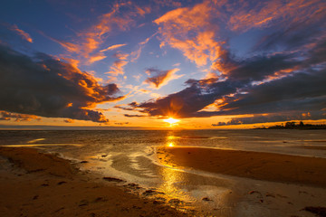 Sunset over the water. Orange sunset. Sunset at low tide.
