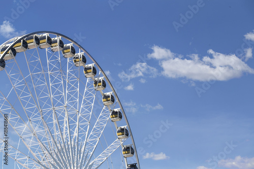Leinwandbild Motiv Giant Ferris wheel with numbered cabins in the park - Bright blue sky with sharp clouds behind it.