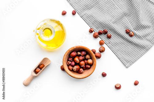 Use nut oil as cosmetics. Hazelnut oil in jar near hazelnut in bowl on white background top view