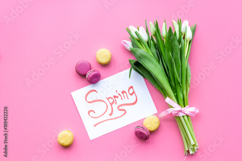 Foto Murales Pale pink spring tulips near word spring and macarons on pastel pink background top view