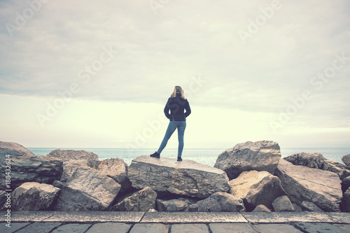 woman standing on the rock at the seaside, blonde young lady looking far away
