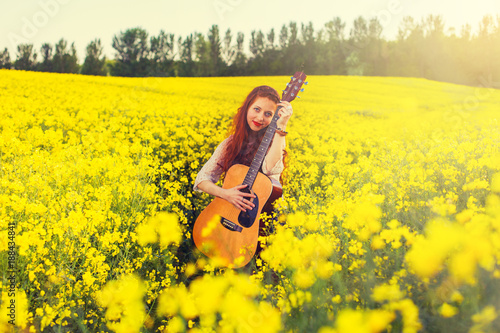 Young ginger hair girl in 70s style with acoustic guitar