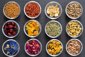 Selection of dried herbs on a dark background, top view