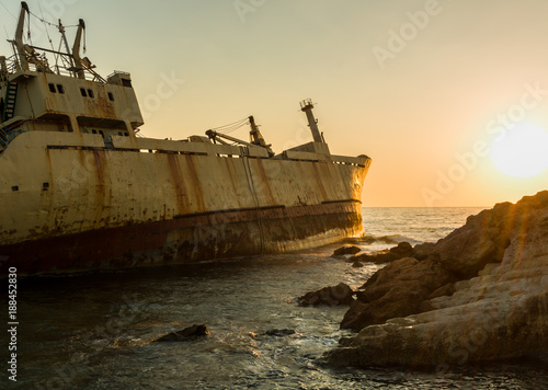 Papiers peints Naufrage Shipwreck at rocky shore with sunset at the sea