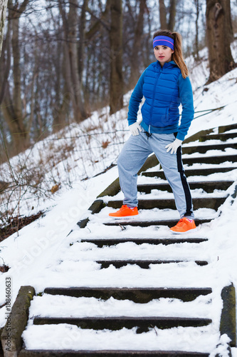Woman wearing sportswear exercising outside during winter - 188460633