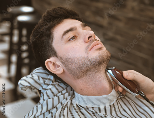 Shave beards in barbercos. A beautiful guy shaves a beard. Body care.
