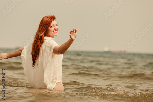 Redhead woman playing in water during summertime