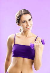 Woman in fitness wear with dumbbell, on rose