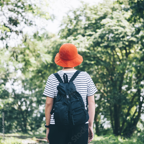 Foto Murales Traveller Hipster with backpack in green forest Landscape Wanderlust Adventure travel Nature explore