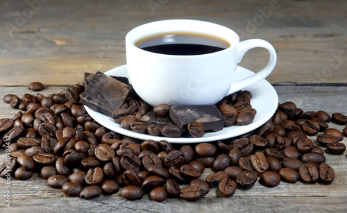 White cup of coffee with a bunch of coffee beans and pieces of chocolate on a wooden table