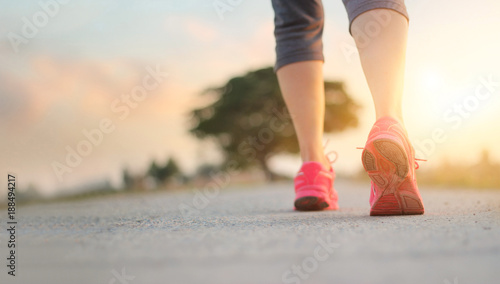 Leinwanddruck Bild Athlete woman walking exercise on rural road in sunset background, healthy and lifestyle concept