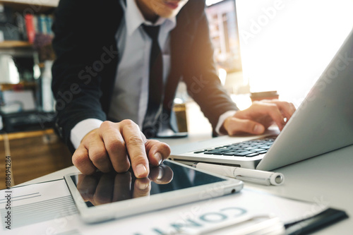 Foto Murales  businessman hand working with laptop computer in modern office with virtual icon diagram at modernoffice in morning light