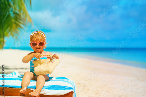 Foto Murales cute little girl with bag relax on tropical beach