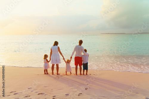 szczęśliwa rodzina z dziećmi chodzić na zachód słońca plaży