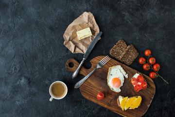 flat lay with tasty healthy breakfast on wooden cutting board on dark tabletop