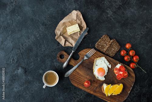 flat lay with tasty healthy breakfast on wooden cutting board on dark tabletop - 188502832