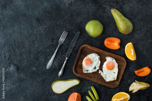 Foto Murales flat lay with healthy breakfast with fried eggs and fruits on dark tabletop