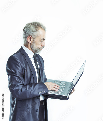 Foto Murales portrait in full growth - experienced businessman with an open laptop on a white background