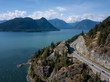 Aerial view of Sea to Sky Highway in Howe Sound during a vibrant sunny summer day. Taken North of Vancouver, BC, Canada.