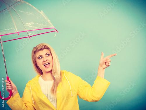 Woman wearing raincoat holding umbrella pointing
