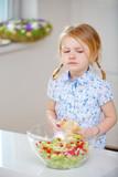 Kind beißt von Brötchen ab in der Küche