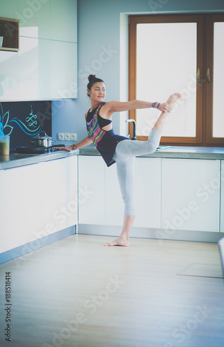 Foto Murales Fitness girl cooking healthy food in the kitchen. Woman. Kitchen. Cooking