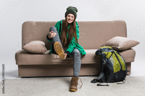 happy girl wearing hiking boots on sofa with backpack