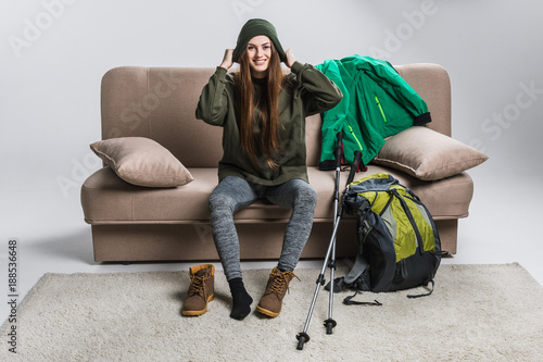 happy traveler wearing hat and hiking boots on sofa with backpack