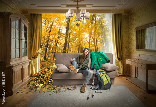 happy traveler sitting on sofa and dreaming about autumn forest