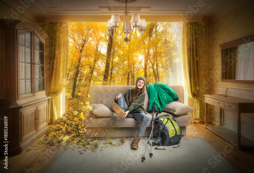 beautiful traveler sitting on sofa and dreaming about autumn forest