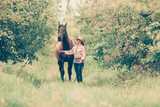 Western woman walking on green meadow with horse - 188538659