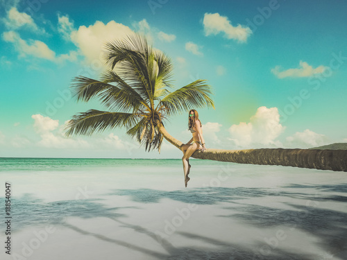 Bikini woman sitting on palm tree at the ocean