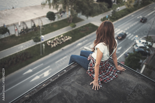 Fridge magnet Young brown haired girl sitting on roof