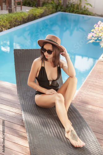 young woman in swimsuit and hat sitting in sun lounge at poolside