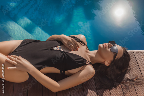 seductive young woman in black swimsuit lying at poolside