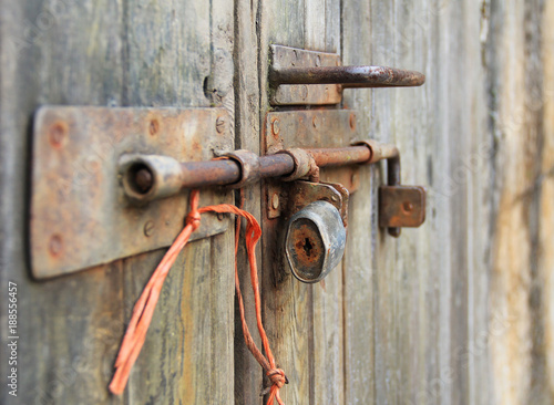 old rusted bolt with locker on the door of a wooden shed