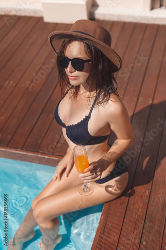 attractive young woman in bikini sitting at poolside with cocktail in glass