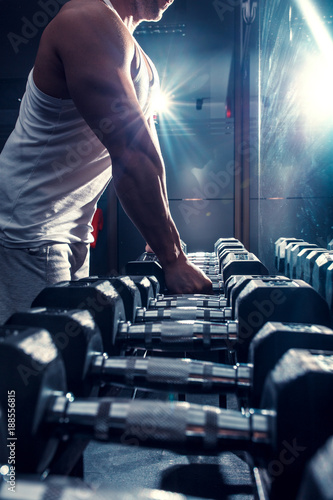 Poster Young man exercising with weight in the gym.Close up.