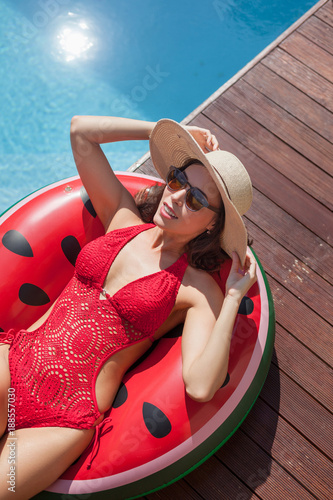 high angle view of attractive young woman in swimsuit relaxing on inflatable ring at poolside
