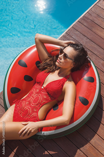 high angle view of beautiful young woman in swimsuit relaxing on inflatable ring at poolside