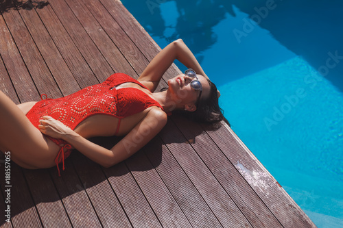 beautiful young woman in swimsuit relaxing at poolside