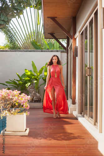 attractive young woman in dress walking by poolside