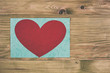 Photo of  red heart on wooden table.