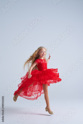 Beautiful blonde girl in red ball-dress jumping at studio