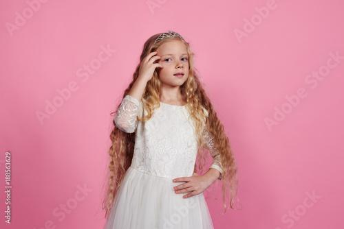 Blonde little girl posing in white dress and diadem