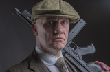 Portrait of a mature Victorian gangster with a machine gun leaning on his shoulder  - 188574033