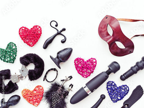 Various sex toys, brown leather Venetian handmade mask and multi-colored braided hearts are on a white background. Image for sex shop advertising or as a funny background for greeting card - 188574638