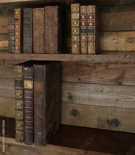 Foto Murales antique books on old wooden shelf.