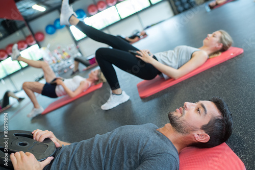 Poster people doing physical exercises on floor at gym